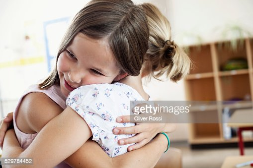 Girls hugging in classroom : Stock-Foto
