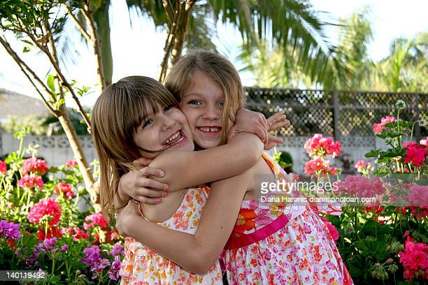 Girls hugging in front of flowers