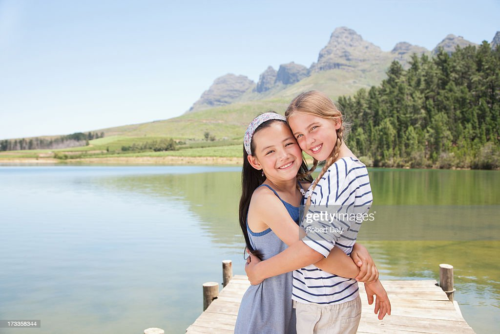 Girls hugging on dock : Stock Photo
