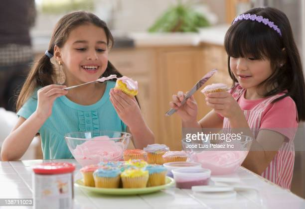 Girls icing cupcakes together