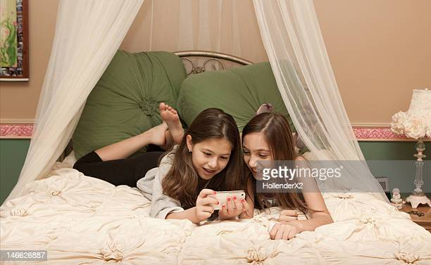 girls in bedroom playing with phone