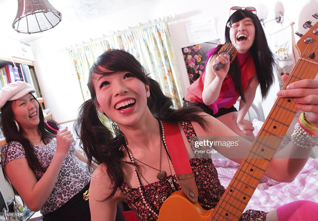girls in bedroom singing and playing guitar : Stock Photo