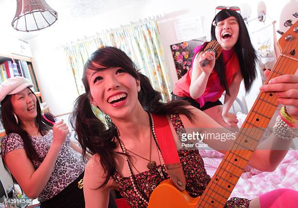 girls in bedroom singing and playing guitar