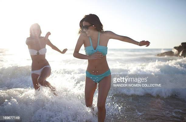 Girls in bikinis running from the waves on beach