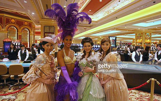 Girls in costume line the entrance to the casino floor prior to doors opening for the first time at the Venetian in Macau 28 August 2007 The world's...
