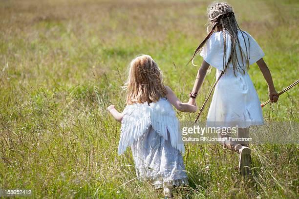 Girls in costumes walking in field