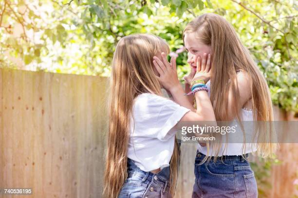 Girls in garden face to face, hands on each others head