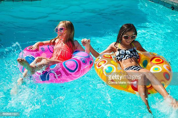 Girls in inflatable rings in swimming pool