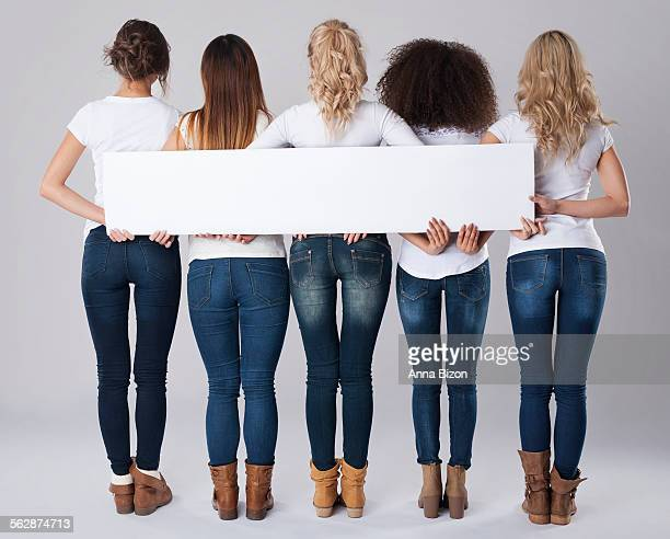 Girls in jeans holding empty banner. Debica, Poland