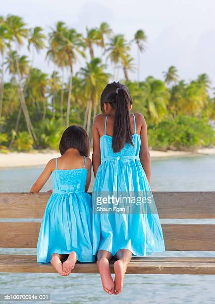 Girls (4-7) in matching dresses kneeling on wooden bench, rear view