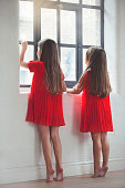 Girls (4-5) in red dresses looking out through window