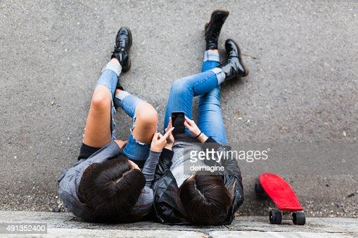 Girls in skatepark sharing smart phone.