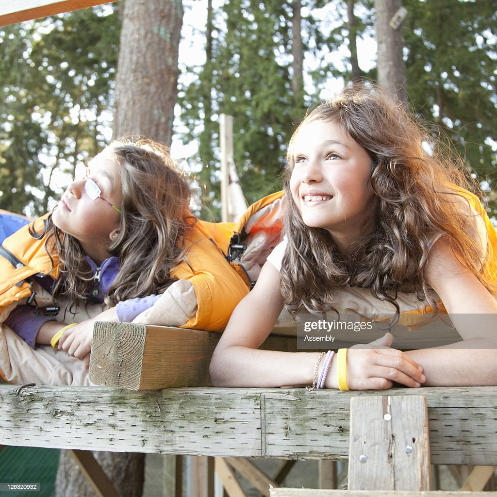 Girls in sleeping bags in a tree fort : Stock Photo