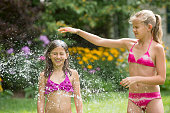 Girls in swimming costume playing with garden sprinkler