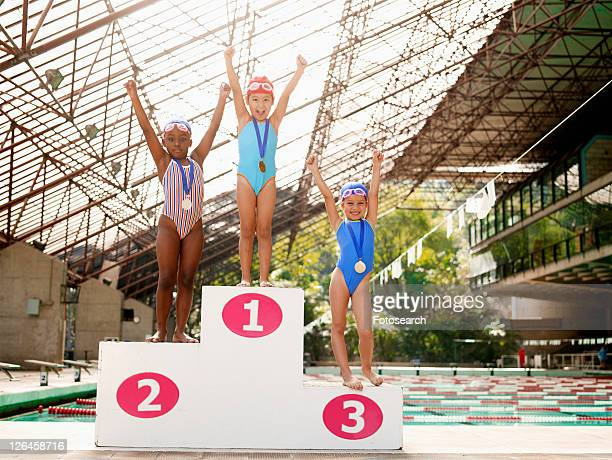 Girls in swimming costumes celebrating on winners podium (portrait)