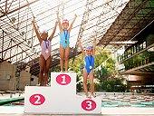 Girls in swimming costumes celebrating on winners podium (portrait)