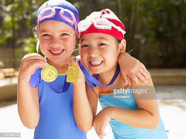 Girls in swimming costumes holding medals (portrait)
