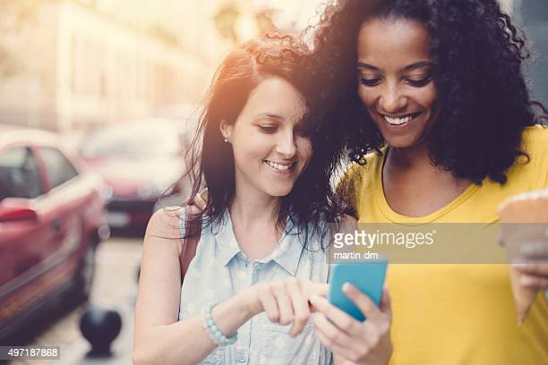 Girls in the city texting on smartphone
