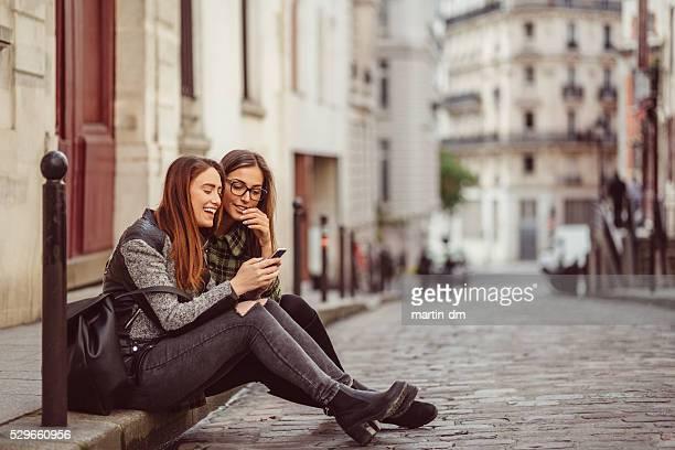 En ville entre filles à envoyer des SMS sur smartphone