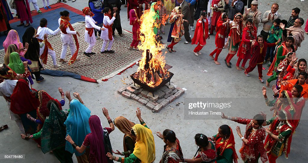 around a bonfire as they celebrate Lohri festival on January 13, 2016 ...