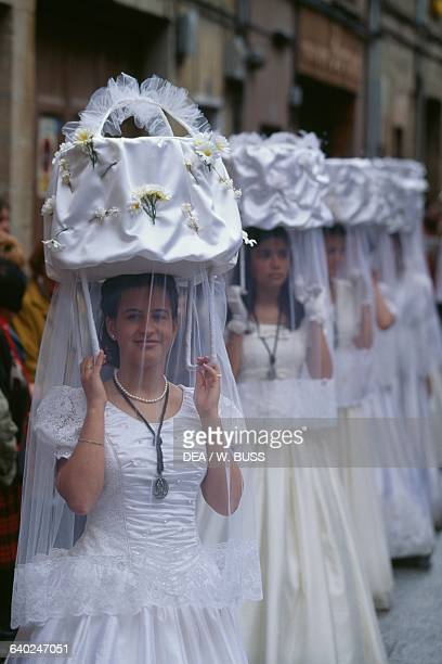 Girls in traditional costume carrying baskets on their head during the procession of the Saint's bread dressed as Las Doncellas Santo Domingo de la...
