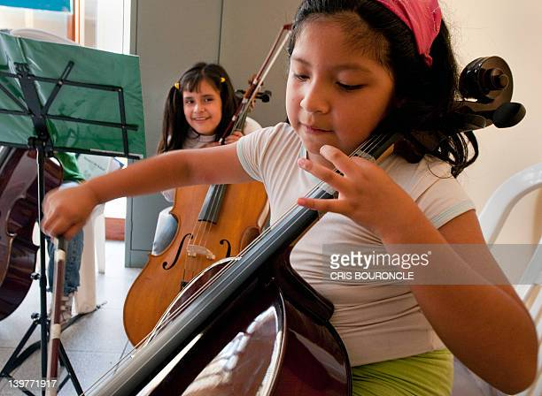 Girls joke while practicing with their cellos at a school in Lima on February 17 2012as part of a social transformation program promoting music in...