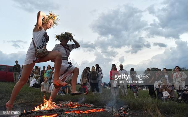 Girls jump over a bonfire during the celebrations of the Ivana Kupala night an ancient heathen holiday in the Pyrogove village near Kiev on July 6...