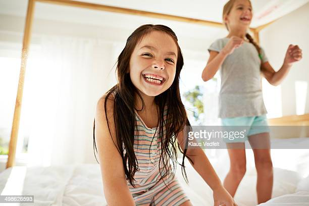 Girls jumping in bed & laughing, back light