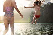 2 girls jumping into a lake