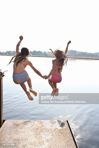 Girls jumping into lake together