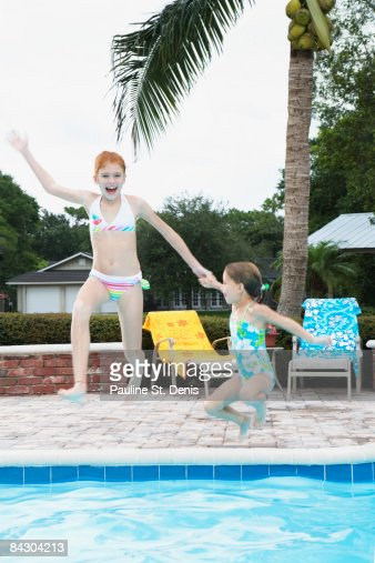 Girls Jumping Into Swimming Pool Stock Photo Getty Images