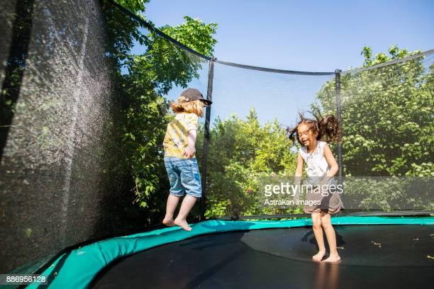 Girls (2-3, 6-7) jumping on trampoline