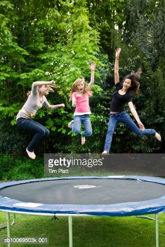 Girls (12-13) jumping on trampoline : Stock Photo