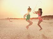 Girls jumping rope on beach