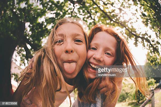 Girls laughing and pulling faces at the camera in park