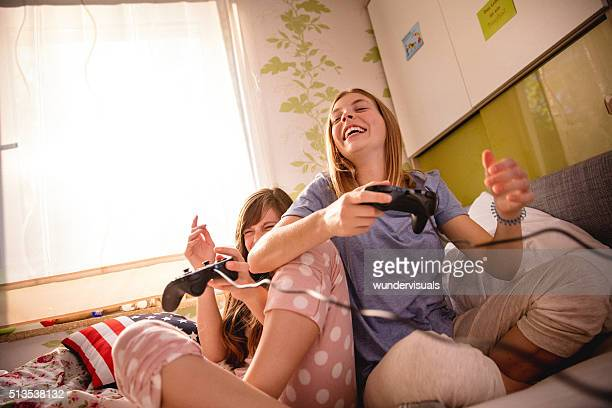 Girls laughing out loud on bed with computer game controls