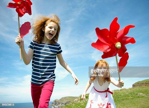 2 girls laughing with red windmills