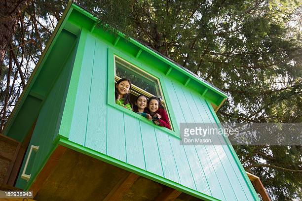 Girls leaning out tree house window
