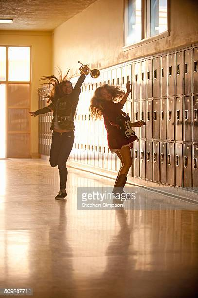 girls leaping in school hallway with instruments