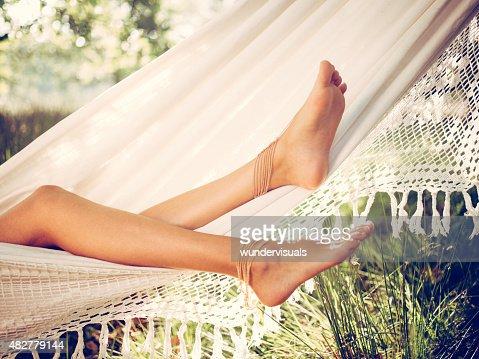 Girl's legs relaxing in a white hammock in summer
