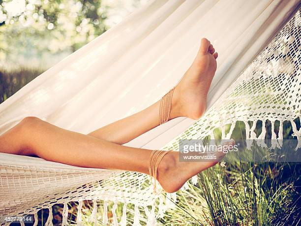Girl's legs relaxing in a white hammock in summer