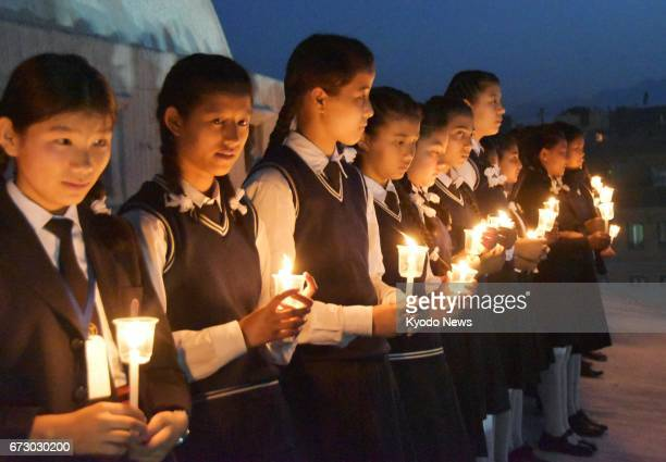 Girls light candles at Boudhanath Stupa in Kathmandu Nepal on April 25 the second anniversary of a devastating earthquake that killed about 9000...