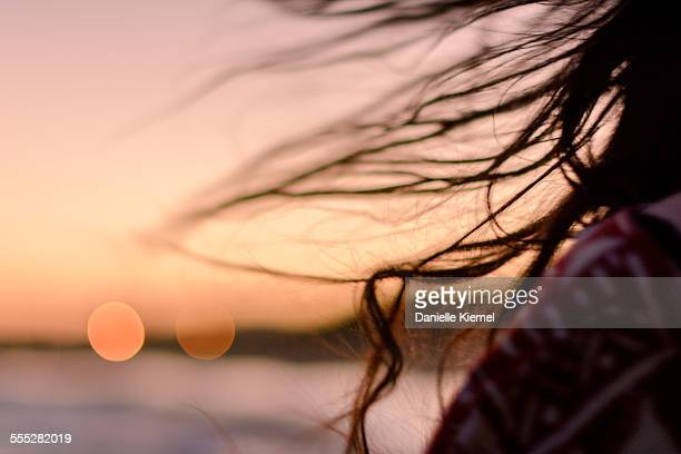 Girl's long hair blowing in sea breeze at sunset