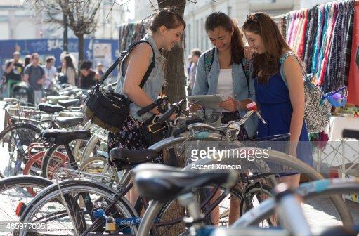 Girls look at digital tablet, school bike stand : Stock Photo