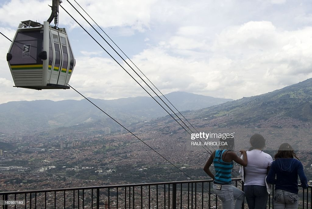 "Girls look down at the city as a Metrocable gondola passes by, in Santo Domingo Savio neighbourhood, in Medellin, Antioquia department, Colombia on March 1, 2013. Medellin, which competed with New York and Tel Aviv, was chosen by popular vote through the internet, as the ""Innovative City of the Year"" during the City of the Year contest, organized by The Wall Street Journal and Citigroup. The distinction was basically made for its modern transportation system, its public library, escalators built in a shantytown and schools that have allowed the integration of society. AFP PHOTO/Raul ARBOLEDA"