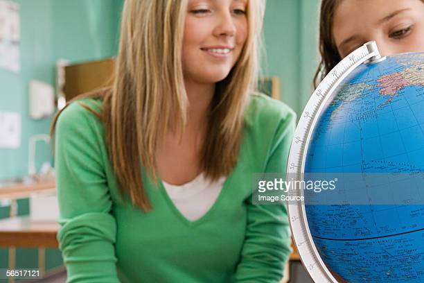 Girls looking at a globe