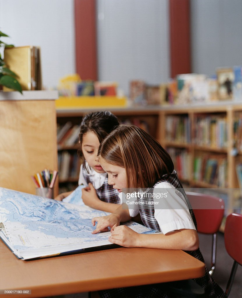 Girls (5-7) looking at atlas in library : Stock Photo