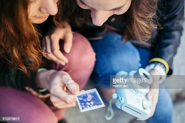 Girls looking at instant photo