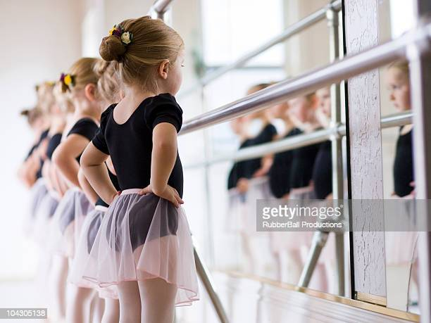 Girls (2-3,4-5) looking at their reflection on ballet class