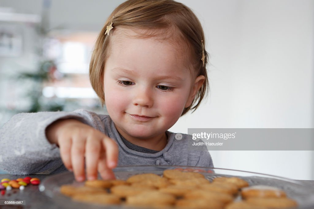 Girls looking down selecting fresh baked cookie smiling : Stock Photo